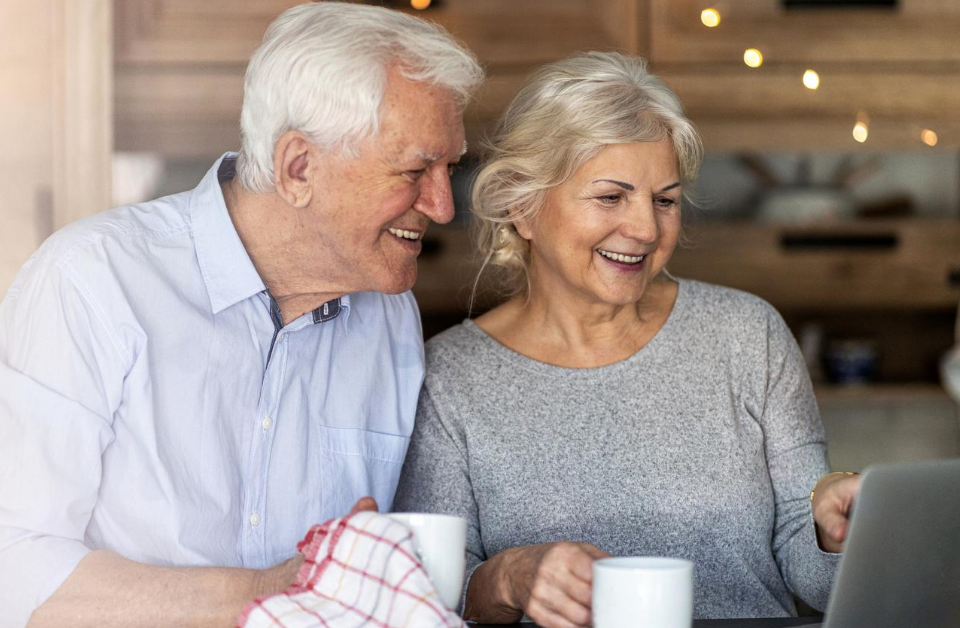 older couple smiling reading about a comfortable retirement