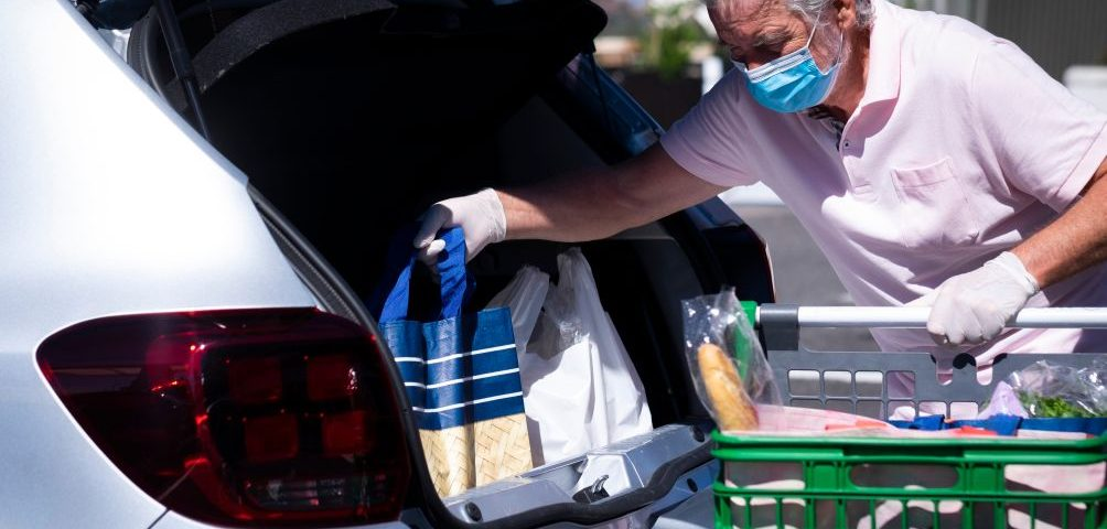 person loading shopping into car demonstrating consumer spending