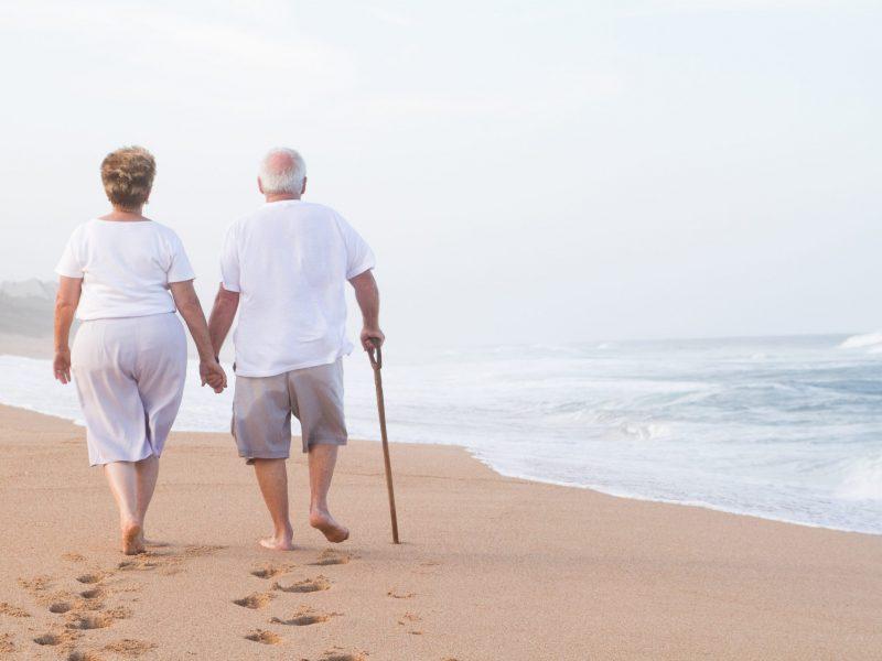 senior couple hand in hand walking on beach